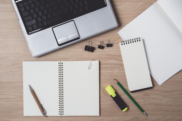Espaço de trabalho com diário ou notebook e laptop, caneta, lápis, caneta hightlight, clipe de metal na madeira