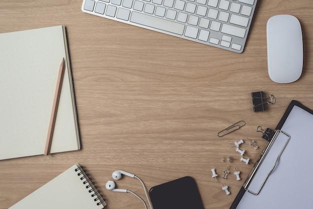 Espaço de trabalho com diário ou notebook e prancheta, computador de mouse, teclado, telefone inteligente, fone de ouvido, lápis, caneta na madeira