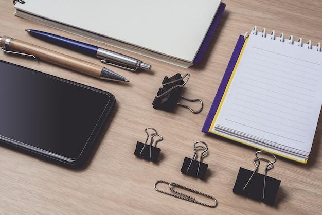 Espaço de trabalho com diário ou notebook e prancheta, telefone inteligente, caneta na madeira