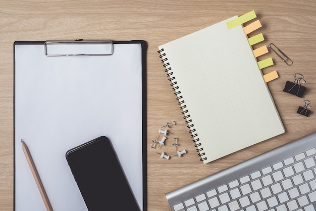 Espaço de trabalho com diário ou notebook e telefone inteligente, prancheta, teclado, lápis, notas sobre madeira