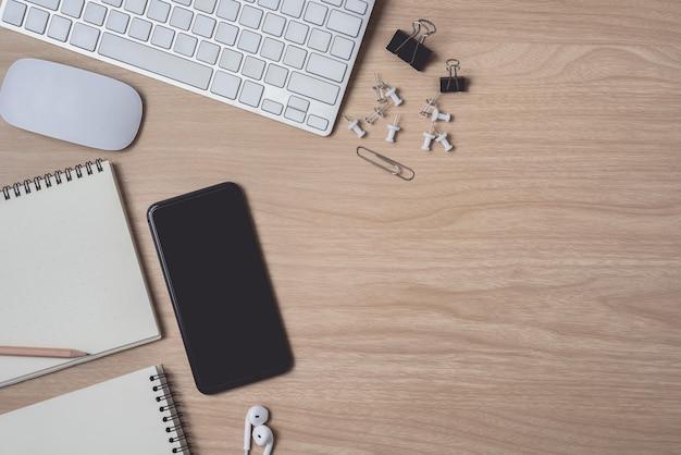 Espaço de trabalho com diário, pranchetas, mouse computador, teclado e smartphone