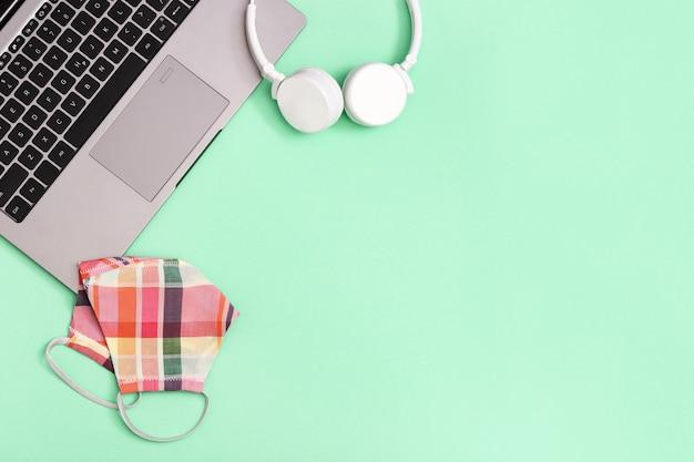 Espaço de trabalho com equipamentos de proteção individual e laptop cinza, fones de ouvido brancos