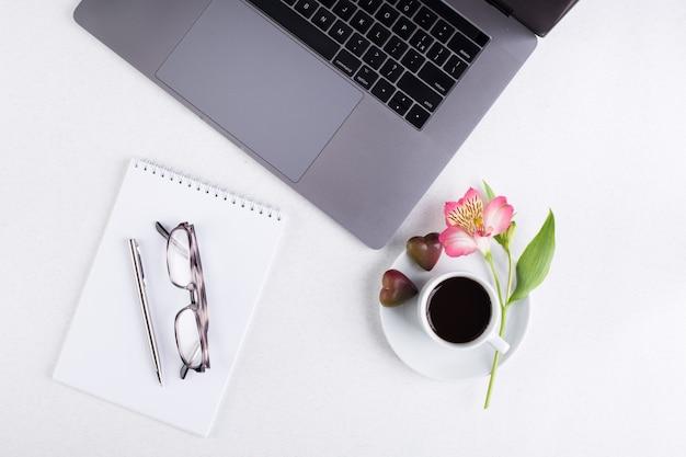 Espaço de trabalho com laptop, bloco de notas, tablet, óculos, xícara de café preto e uma flor de lírio peruano em um fundo branco