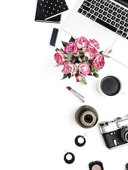 Espaço de trabalho com laptop, buquê de flores rosa, câmera retro, acessórios e cosméticos na superfície branca. camada plana, vista superior