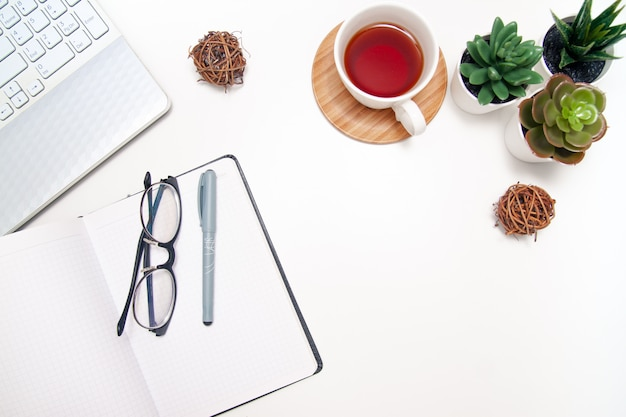 Espaço de trabalho com laptop, caderno, caderno, suculento, xícara de chá