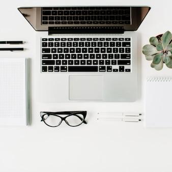 Espaço de trabalho com laptop, diário, suculenta e óculos em branco.