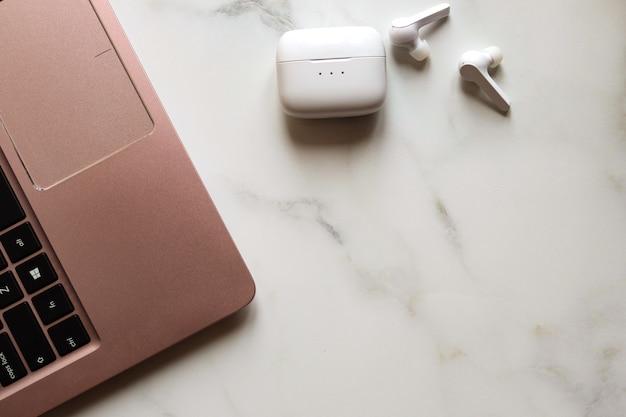Espaço de trabalho com laptop e fones de ouvido sem fio sobre fundo branco. conceito de local de trabalho de freelancer ou estudante.