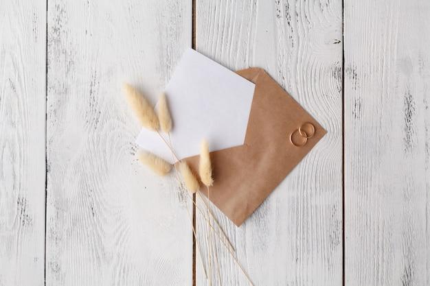Espaço de trabalho com laptop, listas de convites artesanais, envelope de artesanato, caneta, barbante, velas e pinturas em aquarela em branco