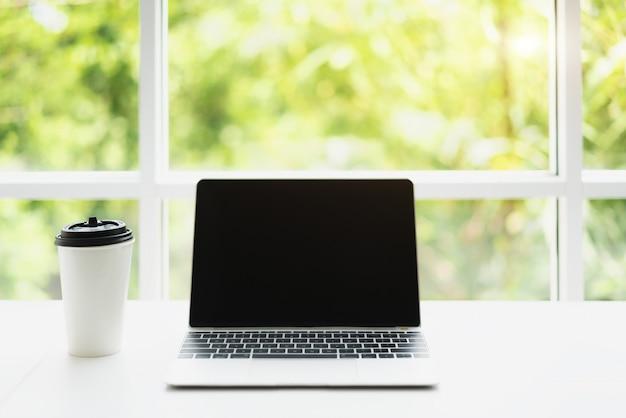 Espaço de trabalho com laptop moderno e caneca de café na planta turva fundo verde na manhã