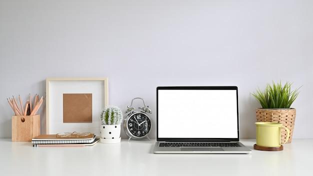 Espaço de trabalho com laptop, molduras para fotos, café, decoração de plantas, lápis na mesa de escritório.