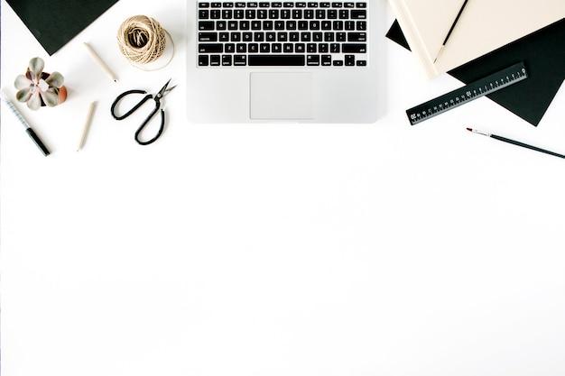 Espaço de trabalho com laptop, tesoura, lápis, suculenta e diário em branco.