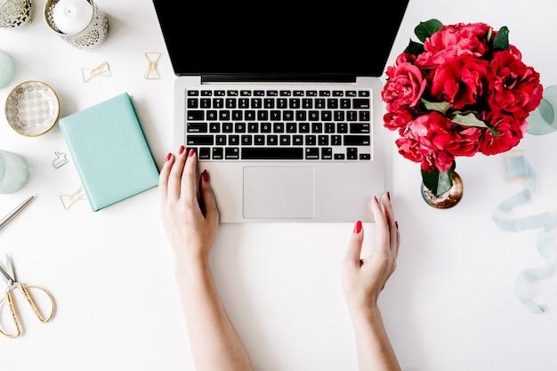 Espaço de trabalho com mãos de menina, laptop, buquê de rosas vermelhas, diário de hortelã, caneca de café e tesoura dourada em branco