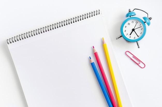 Espaço de trabalho com material escolar, caderno, lápis coloridos e relógio. lay plana ..