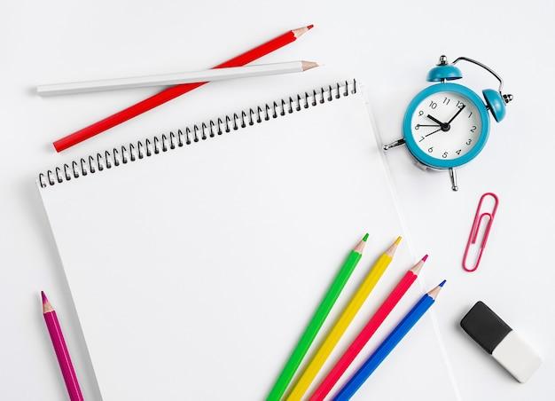 Espaço de trabalho com material escolar, caderno, lápis coloridos e relógio. postura plana, cópia espaço.