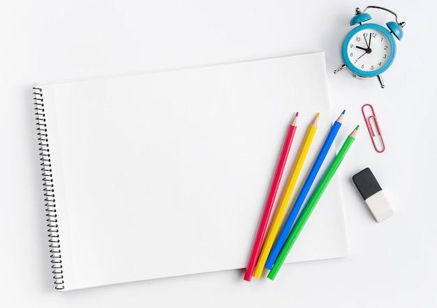 Espaço de trabalho com material escolar, maquete de caderno, lápis coloridos e relógio. lay plana ..