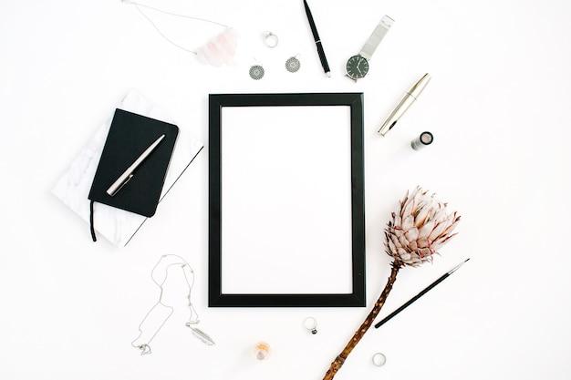 Espaço de trabalho com moldura de foto de tela em branco, relógios de notebook com flor protea e acessórios femininos em fundo branco vista plana de cima mesa de escritório doméstico