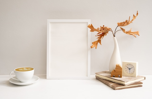 Espaço de trabalho com moldura de pôster de madeira branca simulada, xícara de café, folhas secas de filodendro em vaso relógio modelo de casa em mesa bege