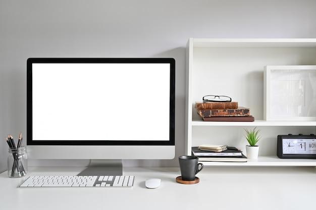 Espaço de trabalho com o computador imac na mesa de escritório e livros, moldura e livros nas prateleiras.