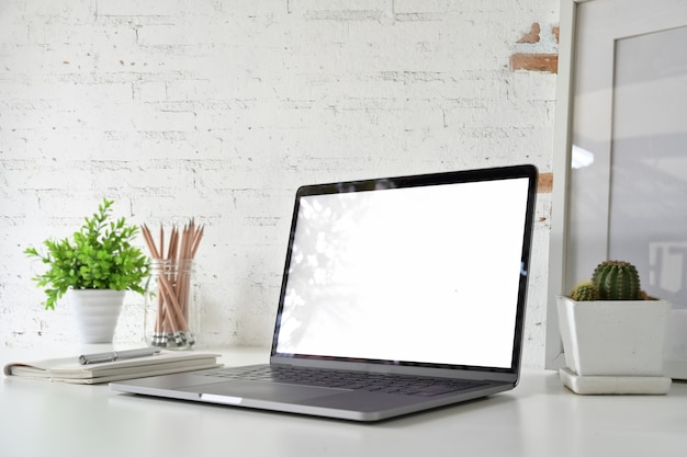 Espaço de trabalho com o portátil em branco da tela branca na mesa do sótão.