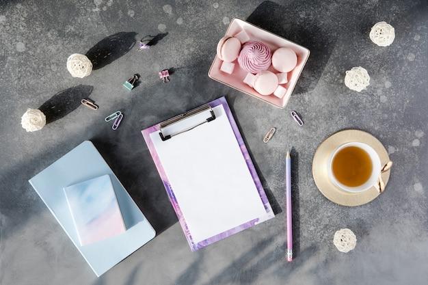 Espaço de trabalho com placa de grampo em branco, material de escritório, lápis e xícara de chá