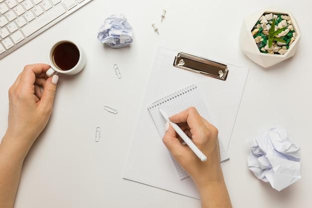 Espaço de trabalho com placa de grampo em branco, teclado, caneta, bola de papel amassado, cacto em uma xícara de café e panela