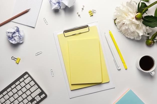 Espaço de trabalho com placa de grampo em branco, teclado, material de escritório