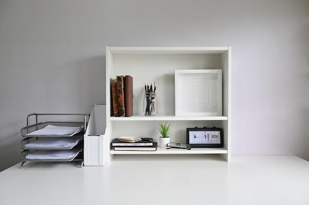 Espaço de trabalho com prateleiras e material de escritório na mesa.