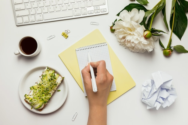 Espaço de trabalho com teclado em branco, mão feminina, notebook, material de escritório