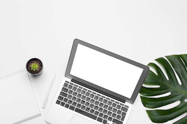 Espaço de trabalho com teclado, folha de palmeira e acessórios. vista plana, cópia superior vista espaço