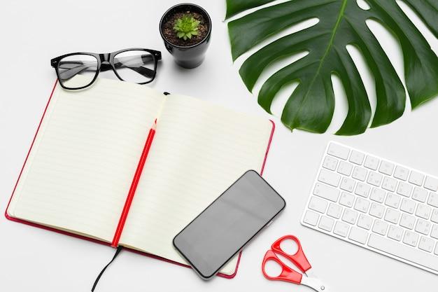 Espaço de trabalho com teclado, folha de palmeira e acessórios. vista plana, espaço de cópia de vista superior