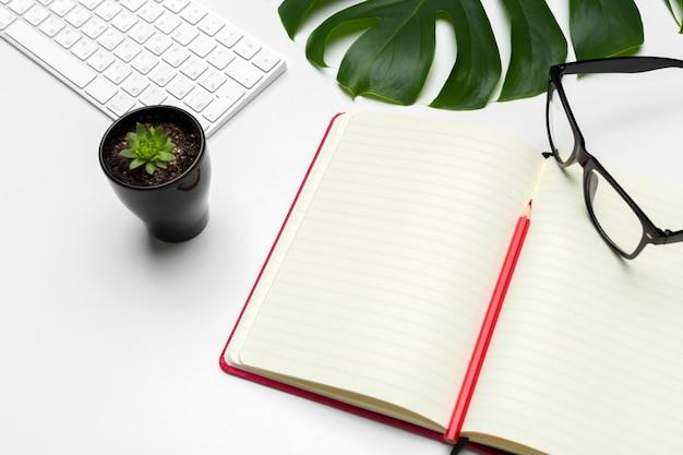 Espaço de trabalho com teclado, folha de palmeira e acessórios. vista plana leiga