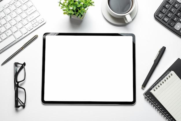 Espaço de trabalho com tela de tablet em branco e equipamento de trabalho em uma mesa branca