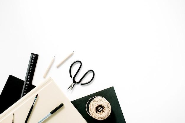 Espaço de trabalho com tesoura, lápis, suculenta e diário em branco.