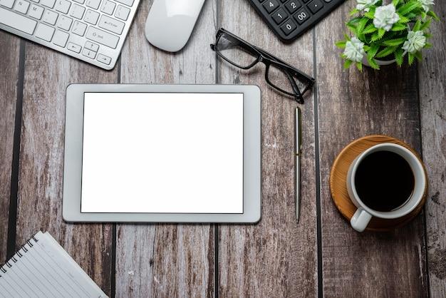 Espaço de trabalho com um tablet uma tela branca e equipamentos de trabalho colocados sobre a mesa de madeira no escritório. brincar.
