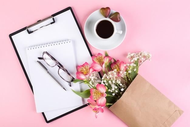 Espaço de trabalho com uma xícara de café expresso, caderno, tablet, óculos e flores de gypsophila e lírio peruano em um fundo rosa