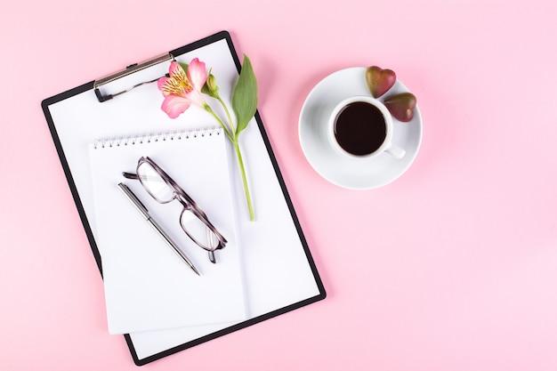 Espaço de trabalho com uma xícara de café expresso, caderno, tablet, óculos e flores de lírio peruano em um fundo rosa