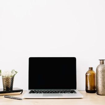 Espaço de trabalho com vista frontal do laptop com tela preta em branco e fundo branco