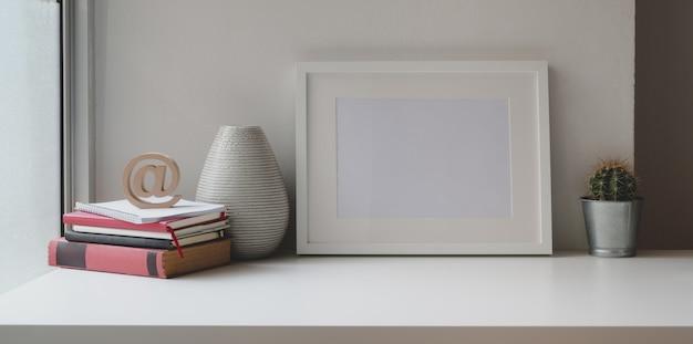 Espaço de trabalho confortável com moldura mock up, material de escritório e espaço para cópia