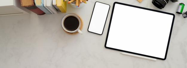 Espaço de trabalho confortável com tablet de tela em branco, smartphone, xícara de café, livros e artigos de papelaria