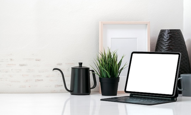 Espaço de trabalho confortável de maquete com tablet de tela em branco e teclado mágico, moldura de madeira, caneca, pote e planta de casa na mesa branca com parede de tijolos.