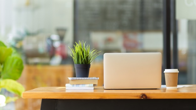 Espaço de trabalho conjunto em cafeteria com maquete de computador laptop, xícara de café, livros, planta na mesa de madeira