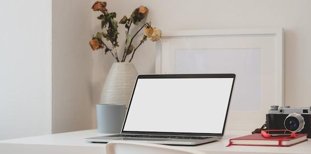 Espaço de trabalho contemporâneo com computador laptop, câmera, material de escritório e vaso de rosas secas