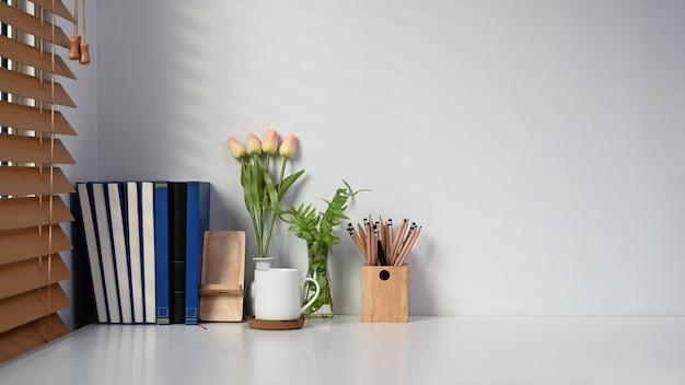 Espaço de trabalho contemporâneo com livro, xícara de café, porta-lápis e flores na mesa branca.