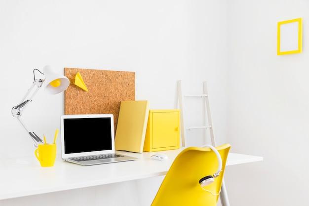Espaço de trabalho criativo brilhante com detalhes amarelos e placa de cortiça