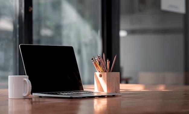Espaço de trabalho criativo de maquete com computador laptop de tela preta, caneca e caixa de madeira de lápis na mesa de madeira na sala de escritório moderna.