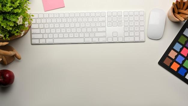 Espaço de trabalho criativo de simulação de cena com teclado de computador, mouse, ferramentas de pintura e espaço de cópia na mesa