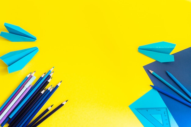 Espaço de trabalho criativo, elegante, minimalista, escolar ou de escritório com suprimentos azuis em amarelo