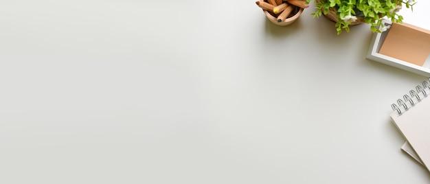 Espaço de trabalho criativo plano com vaso de plantas de papelaria e espaço de cópia