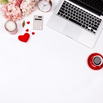 Espaço de trabalho da mesa de escritório domiciliário com portátil e ramalhete cor-de-rosa da hortênsia no fundo branco.