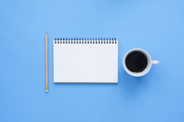 Espaço de trabalho da mesa de escritório - mapeamento de vista plana e vista superior de um espaço de trabalho com a página branca do caderno em branco